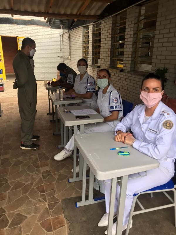 Três servidoras do departamento de Saúde da BM, com uniforme branco, sentadas lado a lado diante de mesas escolares. Em frente a uma delas, em pé, um soldado aguarda a realização do teste para o coronavírus.