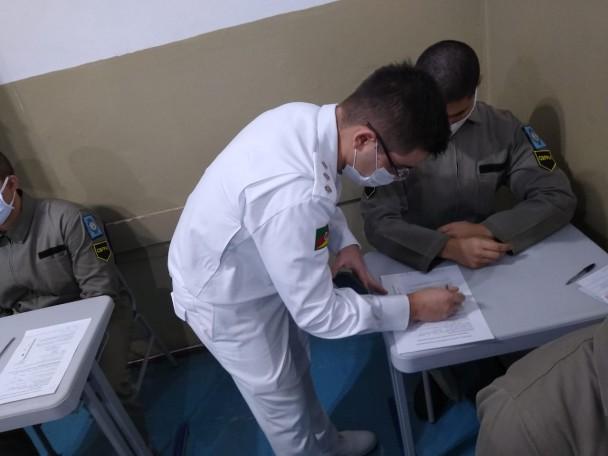 Profissional do Departamento de Saúde da Brigada Militar, de farda branca, aparece em pé, ao lado de uma classe escolar, fazendo anotações em uma folha. Diante da mesa, está sentado um aluno soldado da BM. Ambos utilizam máscaras de proteção no rosto.