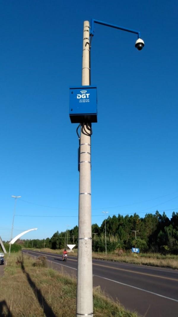 Posto ao lado de uma rua. No alto, uma caixa azul com a sigla DGT. Na extremidade do poste, uma câmera arredondada.