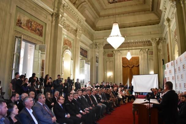 Em salão do Pálacio Piratini, Ranolfo Vieira Júnior, em pé, discursa para uma plateia de autoridades sentada em fileira a sua frente. Ao fundo, profissionais de imprensa acompanham o evento.