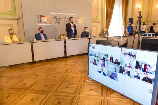 Em pé, atrás de bancada branca, o governador fala ao microfone. À esquerda dele, o vice-governador Ranolfo e a secretária da Saúde, Arita Bergmann. À direita, o deputado Giovani Cherini e o comandante da BM, coronel Morh. À frente, uma grande TV.