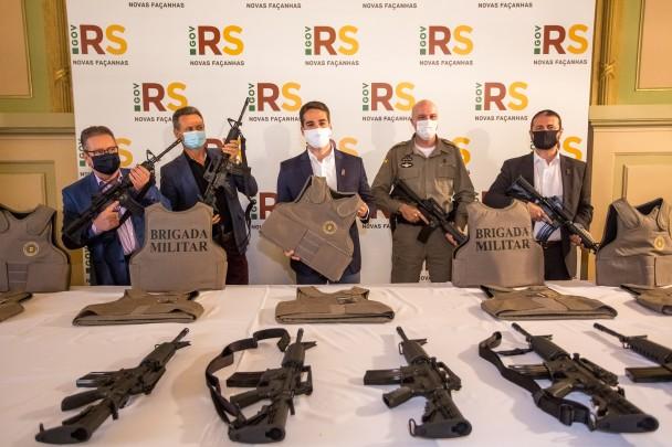 Em pé, diante de uma mesa com coletes e armas, o vice-governador Ranolfo, o deputado Giovani Cherini, o governador Eduardo Leite, o comandante da BM, coronel Mohr, e o secretário adjunto da SSP, coronel Marcelo Frota, seguram armas e coletes.