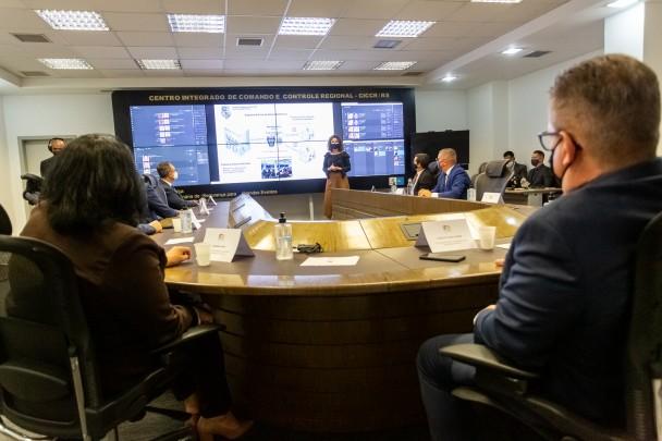 No fundo da imagem, de pé, a diretora geral do instituto geral de perícias a frente de um telão com dados, discursa para as pessoas em torno de uma grande mesa de reuniões