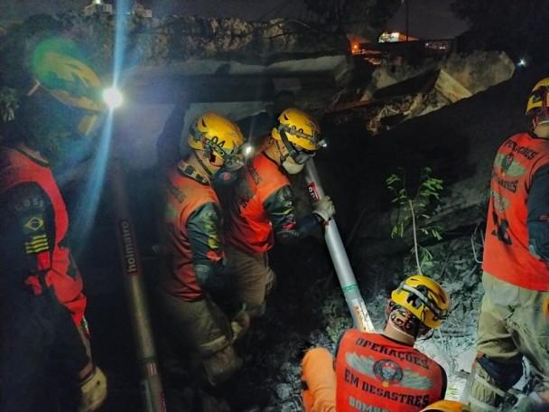Três bombeiros estão de pé com equipamentos de proteção e com lanternas acoplados em seus capacetes. Um outro agente está sentado no chão enquanto segura um objeto com um dos agentes de pé.