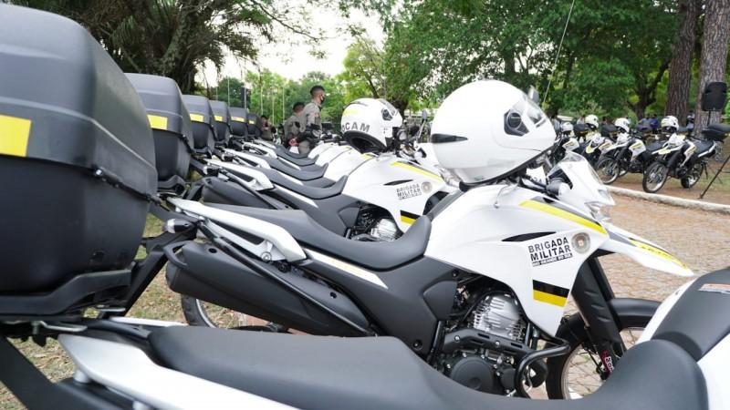 Motocicletas enfileiradas uma ao lado da outra, com o capacete no guidão de cada moto. A foto foi tirada na lateral das motos, possibilitando a captura de mais de 10 motos em uma foto.