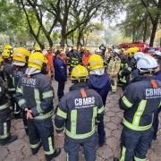 muitos bombeiros equipados, em roda, ouvindo orientações do seu comandante