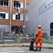 Bombeiro com cão em frente ao prédio destruído da ssp.