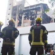 Três bombeiros olham para o prédio destruído da SSP ao fundo.