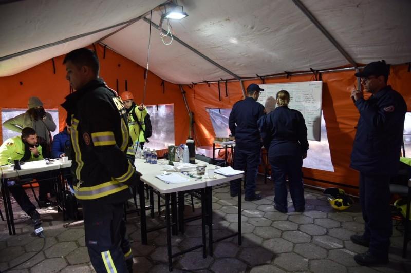 Interior da barraca de Posto de Comando de Operações no pátio da SSP com bombeiros trabalhando.