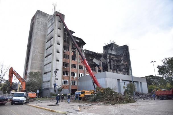 Prédio da SSP, com parte das estruturas desabadas após incêndio, no entorno da estrutura, forte maquinário retira parte dos escombros