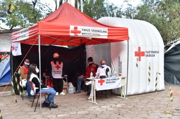 Barraca em lona com estrutura de metal, com a inscrição da Cruz Vermelha, sob a barraca, cinco pessoas participam do atendimento