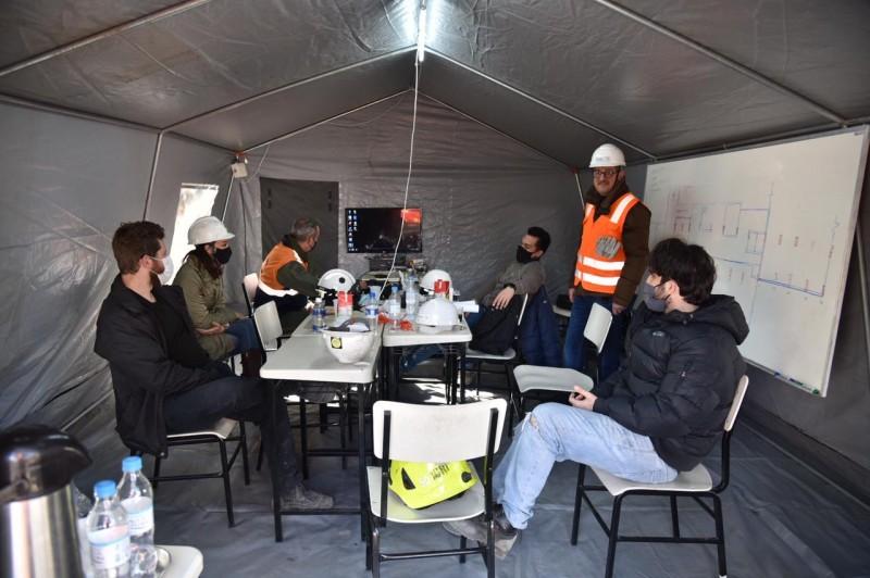 Engenheiros em torno de uma mesa dentro da tenda. À direita, um quadro branco com desenho do prédio.