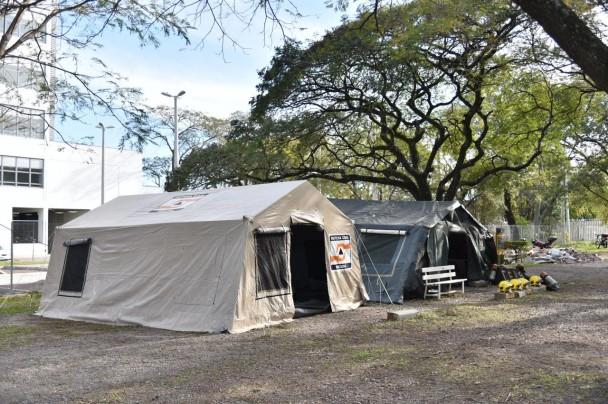 Duas tendas, uma marrom e outra preta, lado a lado no pátio da SSP.