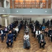 sentados, mantendo o distanciamento, novos delegados acompanhando cerimônia de posse