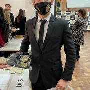 Delegado empossado em foto com o distintivo e a camisa da instituição
