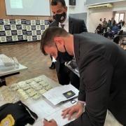 Delegado empossado assina documento para pegar distintivo e camiseta